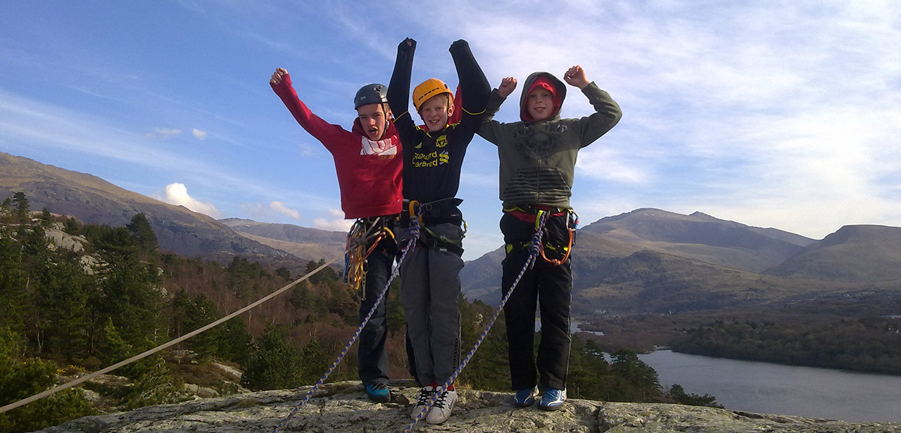 A young team celebrate upon reaching the top of their first climb