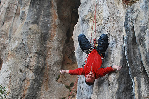 A small image of a climber hanging upside down on a rope