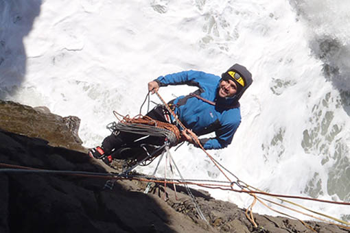 A small image of a climber hanging on a cliff above the crashing waves