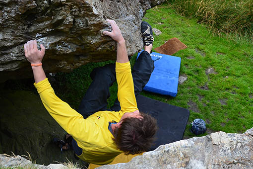 A small image of a climber climbing holding onto a boulder with his heels
