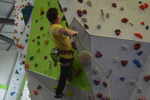 A small image of a climber climbing through an overhanging roof