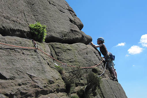 A small image of a climber traversing across a cliff