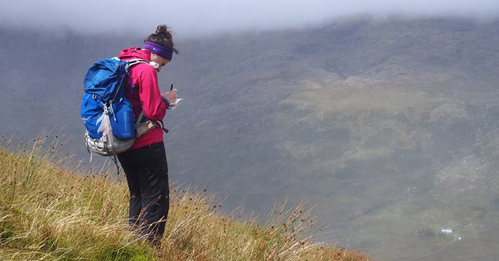 A mountaineer checking her map