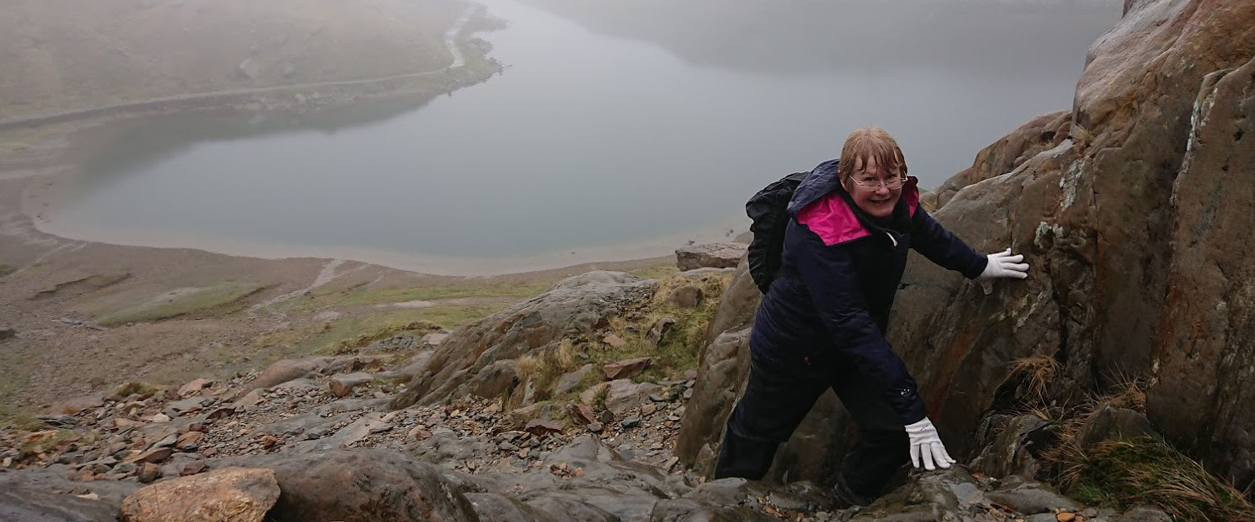 A lady making her way up Snowdon for the first time. Despite what looks like a damp day she is smiling