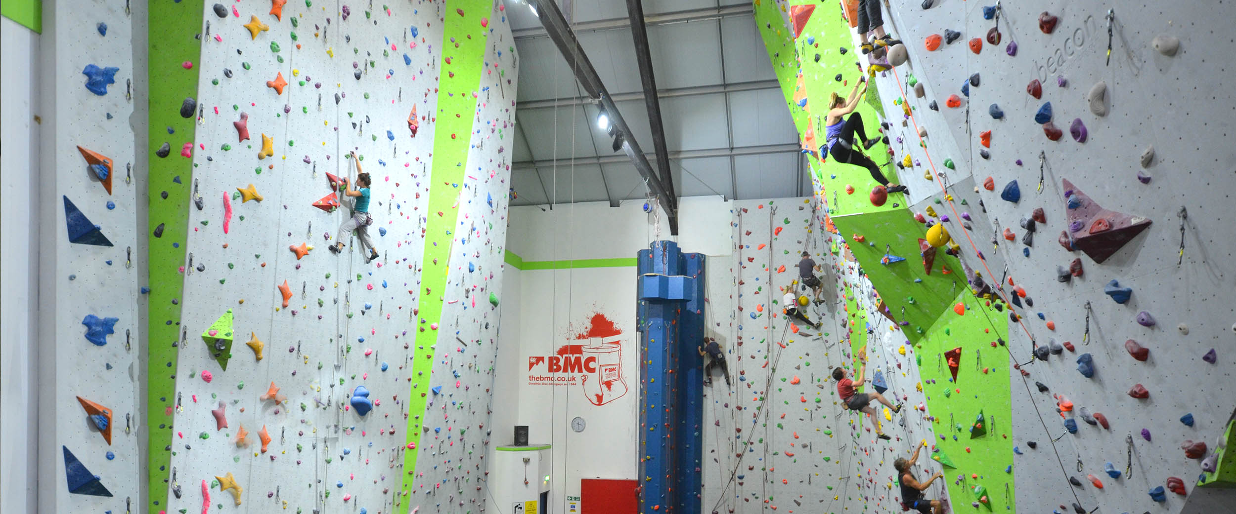 A young girl appears to be extremely focused as she makes her way across a short climbing wall