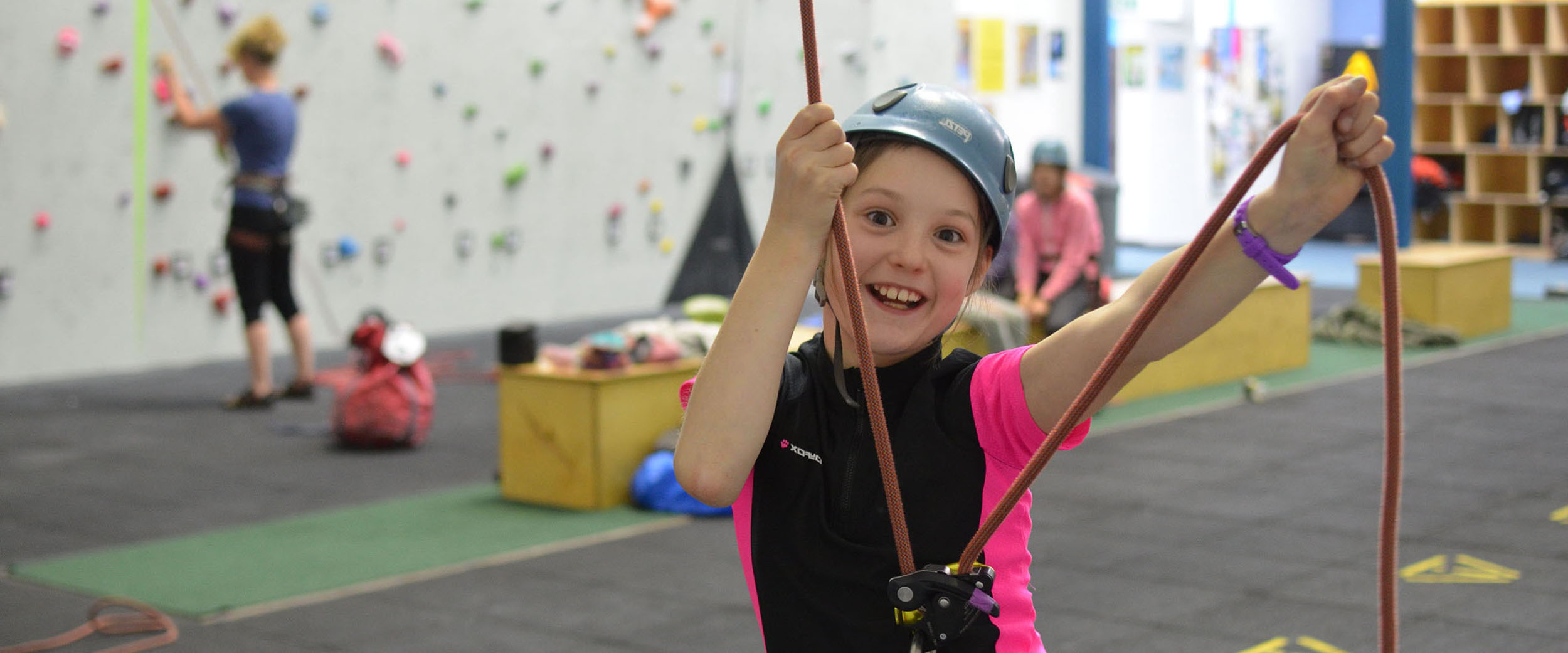 A very happy child holds a rope at an indoor climbing wall