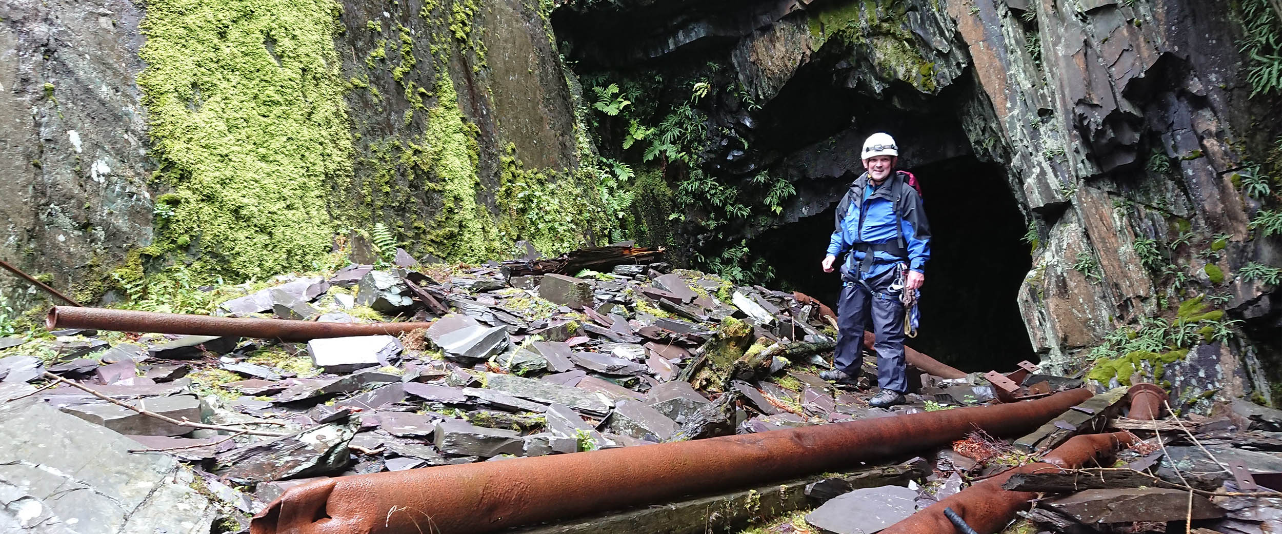 A mountaineer emerges from an old mine. The area is covered in moss and remnants of an old industrial age
