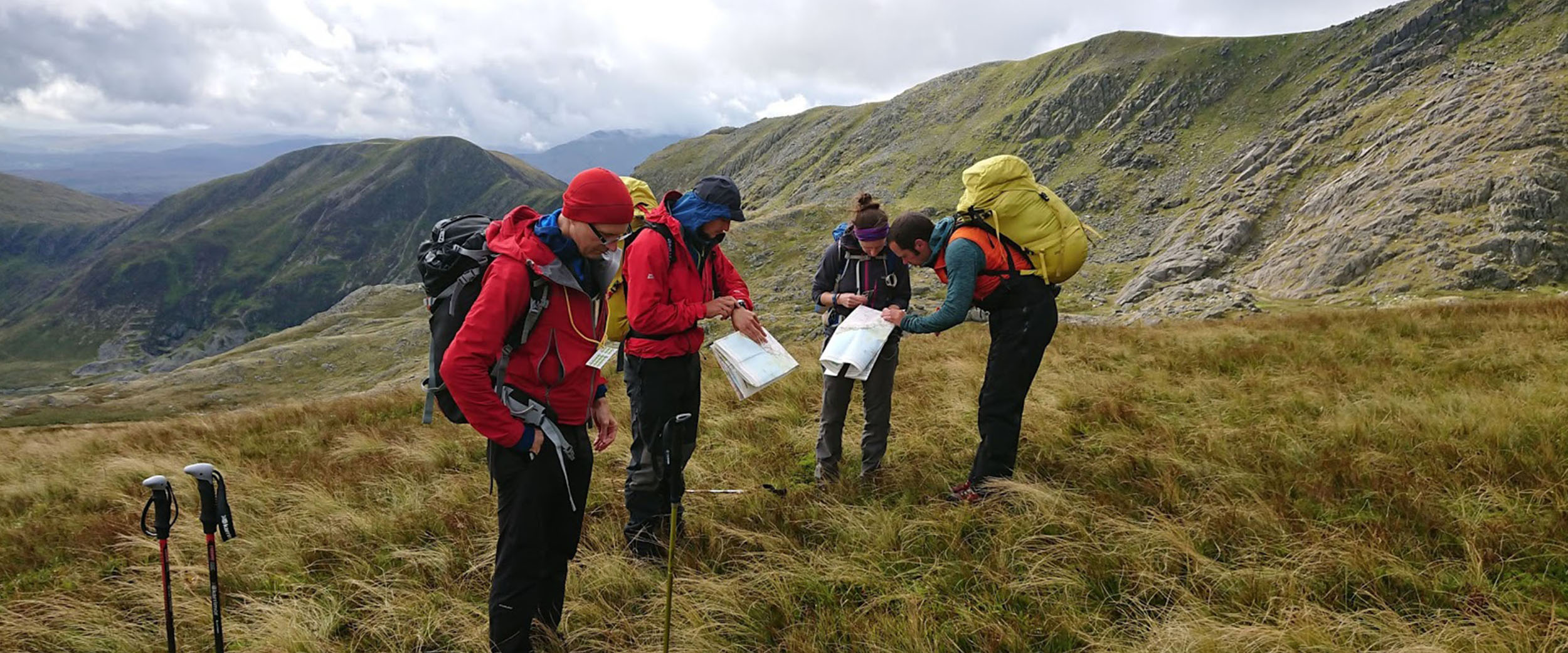 Four mountaineers reading maps on a hillside. One of them looks like an instructor