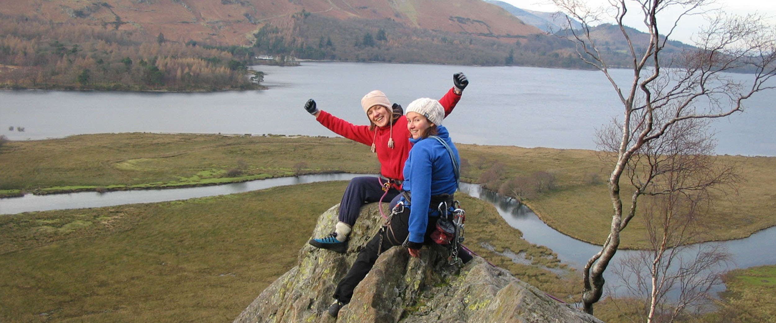 Two young ladies punching the air and congratulating each other having climbed a difficult cliff-face
