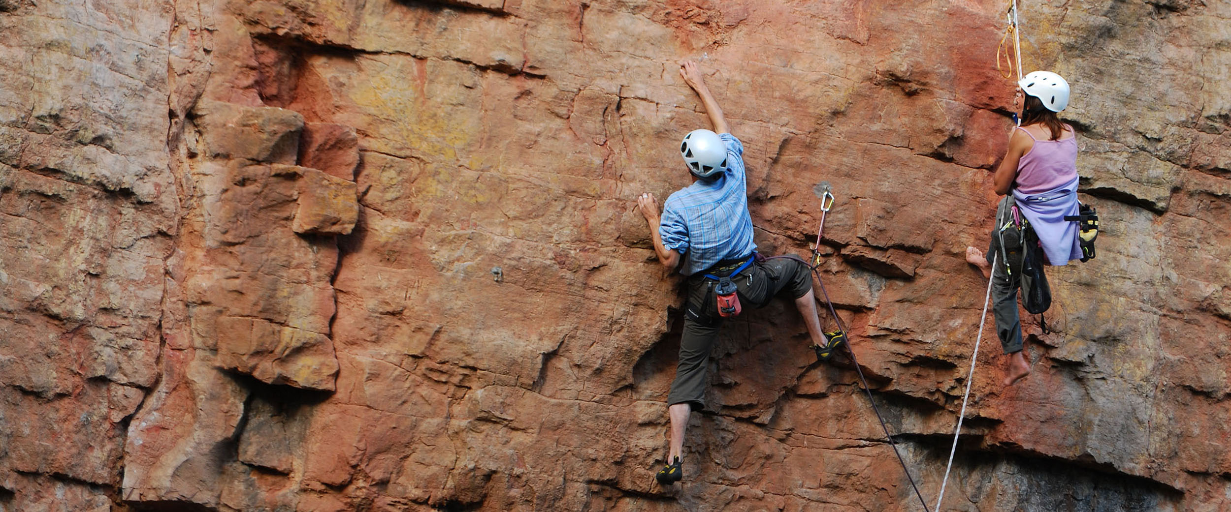 A climbing instructor hangs from a rope and offers advice to their client. The client appears to climbing through a difficult section on a sheer face