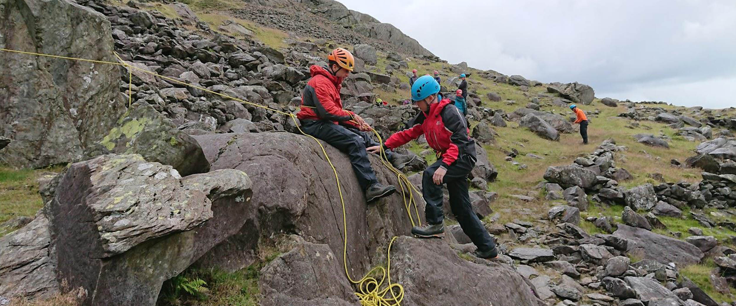 Two mountaineers perched on some boulders demonstrate scrambling rope work